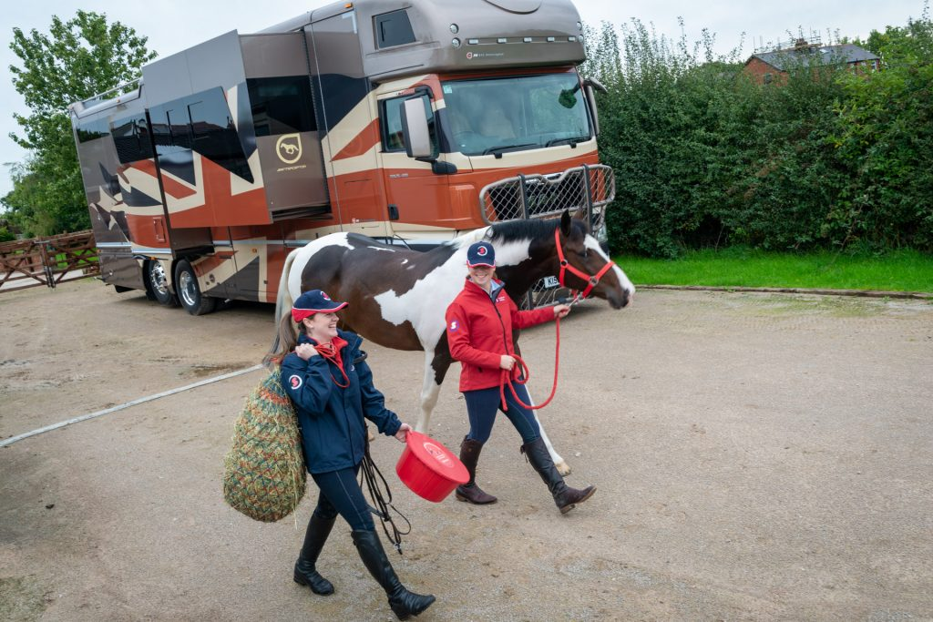 Riders leading horse with haynet and feed bucket, with horsebox in the background